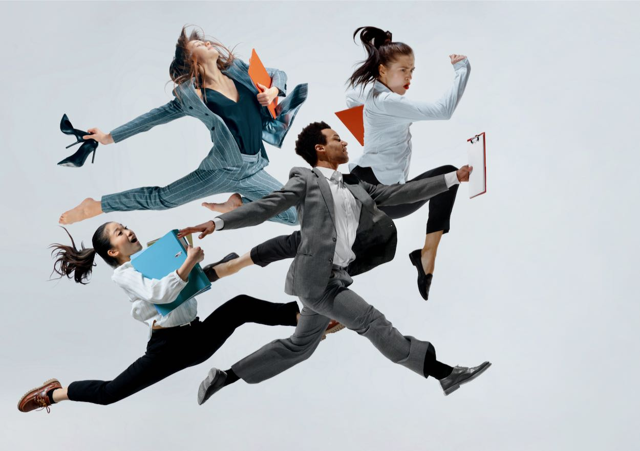 Happy businesswoman and african man dancing in motion isolated on white studio background. Flexibility and grace in business. Human emotions concept. Office, success, professional, happiness, expression concepts