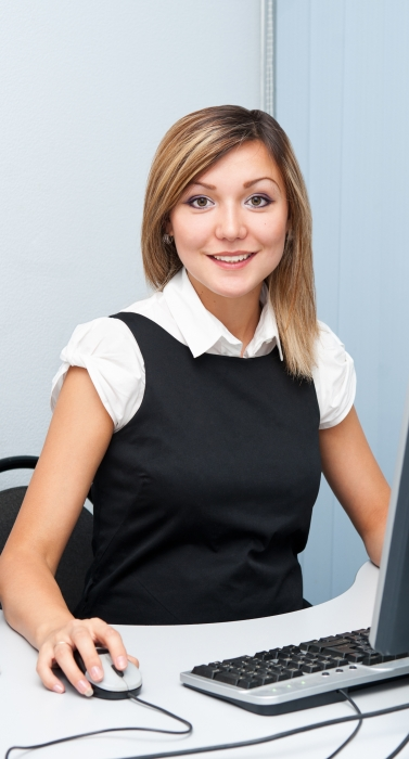 a young caucasian woman sitting in front of a computer looks into camera and smiles