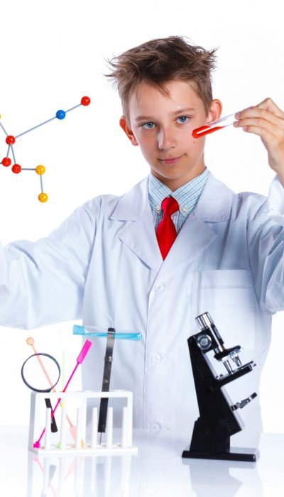 Happy enthusiastic Chemist boy with chemical test tubes and microscope. Isolated on a white background